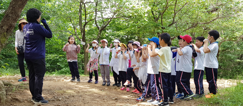 강사와 학생들이 숲속에서 간단한 활동중