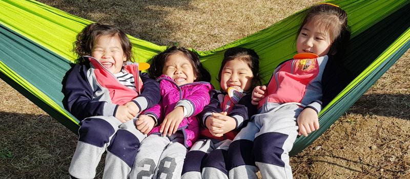 해먹에 4명의 유치원생이 누워 웃고있다