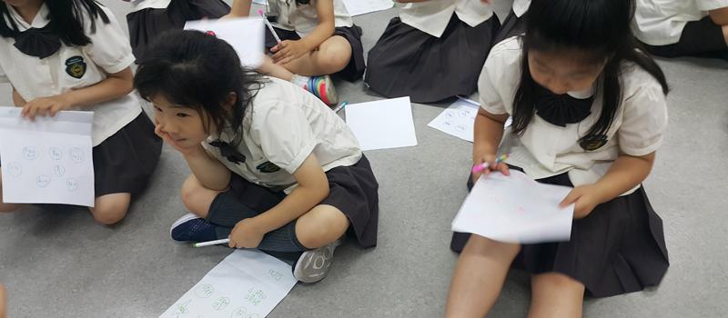학생들 바닥에 앉아 필기중
